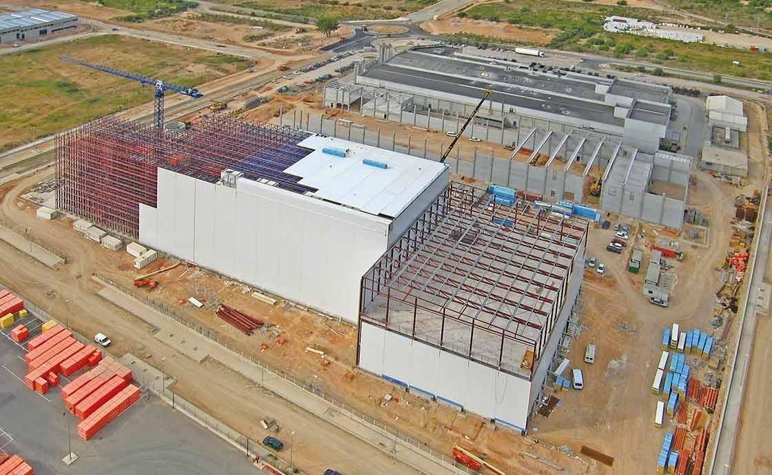 Warehouse construction with integral rack-supported systems, prepared to withstand earthquakes or strong gusting wind.