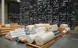 Extending imposingly 30 feet in the air, thousands of fabric rolls bunk in shelving compartments like crayons in a box